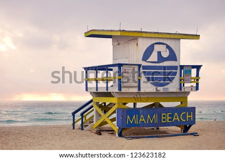Summer scene in Miami Beach Florida, with a colorful lifeguard house in a typical Art Deco architecture, moments before sunrise with blue sky in the background. Light painting - stock photo