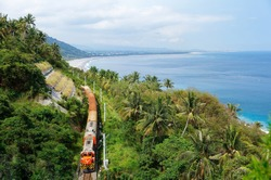 Summer scene of a Chu-Kuang Express train traveling on the green wooded hillside overlooking a white sandy beach on the beautiful coastline by the blue Pacific Ocean, in Taimali, Taitung, Taiwan, Asia