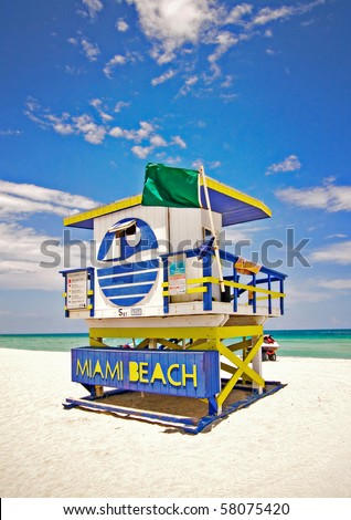 Summer scene with a typical colorful lifeguard house in Miami Beach, Florida with blue sky and ocean in the background