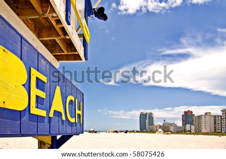 Summer scene with a typical colorful lifeguard house in Miami Beach, Florida with blue sky and skyscrapers in the background