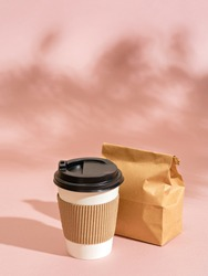 Summer scene with eco friendly paper cup, breakfast to go in paper packaging on pink background with foliage shadow. Perfect millennial breakfast. Recycling concept. Street food or snack. Copy space.