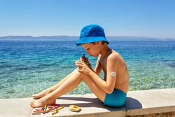 Summer sea holidays: a boy with sugar monitoring system sitting on the beach and draws on pebbles. Concept life with diabetes, glycemic control. Children's creativity in the fresh air on vacation