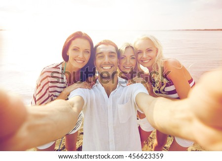 summer, sea, tourism, technology and people concept - group of smiling friends with camera on beach photographing and taking selfie #456623359