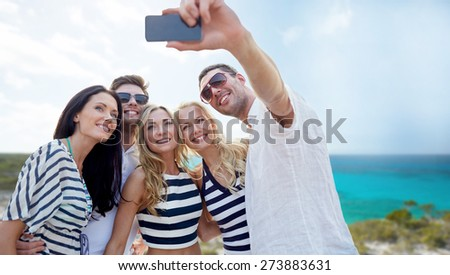 summer, sea, tourism, technology and people concept - group of smiling friends with smartphone photographing and taking selfie on beach