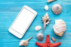 Summer sea vacation concept background with copy space. Blank screen mobile phone and various seashells and a red starfish on a blue wooden floor background.