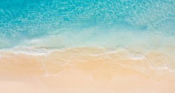 Summer seascape beautiful waves, blue sea water in sunny day. Top view from drone. Sea aerial view, amazing tropical nature background. Beautiful bright sea with waves splashing and beach sand concept