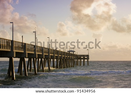 Summer serene scene with fishing pier, cloudy sky and the ocean during sunrise in the morning. Shot near tropical travel destination of Miami Beach Florida. Copy space for your text.