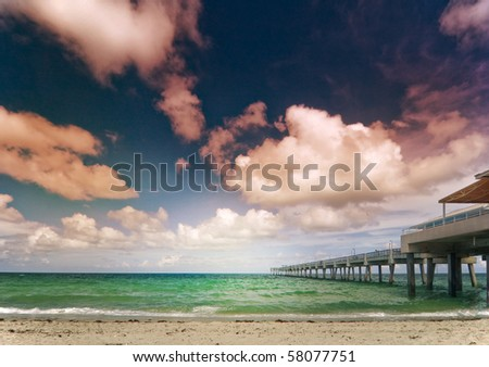 Summer serene scene with pier, cloudy sky and the ocean in the morning. Shot near Miami Beach Florida