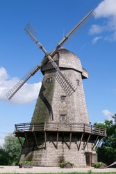 Summer shot of historical old wooden windmill with blue cloudy sky background. Authentic unique wooden windmill with a balcony typical for 18th century for several European countries Denmark, Holland