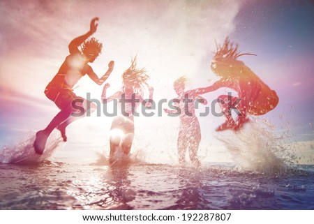 summer silhouettes of happy young people jumping in sea on the beach. vintage retro style with soft focus and sun flare