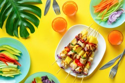Summer simple recipe for grilling, hawaiian chicken kabobs served with freshly diced vegetables and some orange drink in glasses, view from above