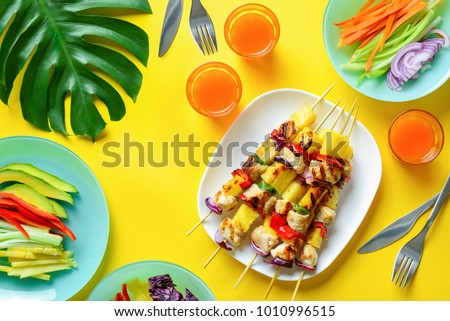 Summer simple recipe for grilling, hawaiian chicken kabobs served with freshly diced vegetables and some orange drink in glasses, view from above  - Shutterstock ID 1010996515