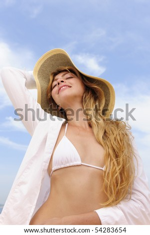 summer: smiling woman with sun hat sunbathing