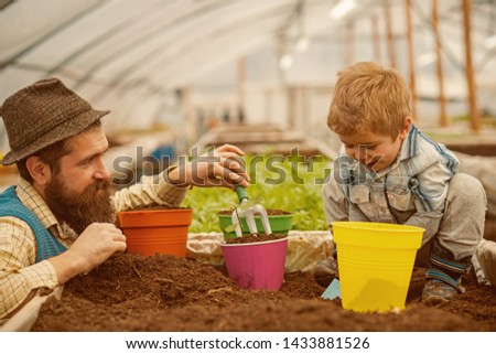 summer. spending great time together. summer is coming. father and son work in summer greenhouse. summer season planting. #1433881526
