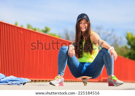 Summer sport and active lifestyle. Cool teenage girl skater sitting on skateboard on the street. Outdoor.