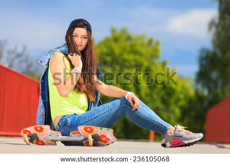 Summer sport and active lifestyle. Cool teenage girl skater sitting with skateboard on the street. Outdoor.