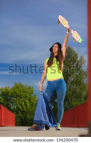 Summer sport and active lifestyle. Cool teenage girl skater with skateboard on the street. Outdoor.