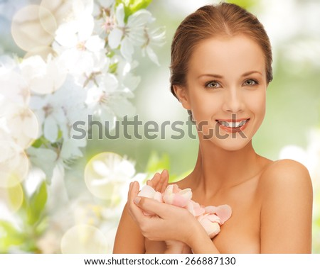 summer, spring, beauty, people and health concept - beautiful young woman holding flower petals over green blooming garden background