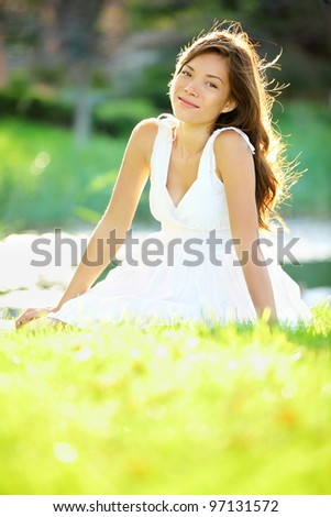 Summer / spring woman smiling happy sitting in white dress in sunny park by lake. Beautiful mixed ethnic Caucasian / Chinese Asian girl outdoor.