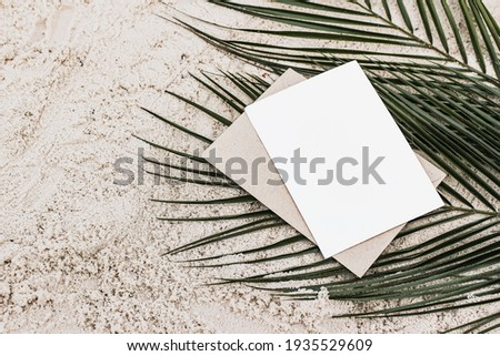 Summer stationery still life. Closeup of blank card mock-up and craft envelope on green date palm leaves. Sandy beach background or desert. Flat lay, top view. Tropical vacation concept.  Foto stock ©