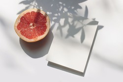 Summer stationery still life scene. Closeup of cut grapefruit fruit on white table background in sunlight. Blank paper cards, invitations mockup scene, long olive branches shadows. Flat lay, top view.