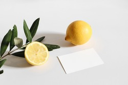Summer stationery still life scene. Cut lemon fruit and olive tree branch nad leaves  in sunlight. Blank business card mockup isolated on white table background. Branding concept, Mediterranean design