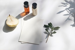 Summer stationery still life scene. Cut pear fruit, cosmetic oil, cream bottles and olive tree branch. White table. Blank paper cards, invitations mockup scene. Long shadows overlay. Flat lay, top