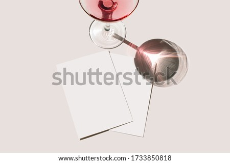 Summer stationery still life scene. Glass of red wine, cocktail, long shadow. Blank greeting cards mockups scene. Pink table background in sunlight. Flat lay, top view. Birthday, celebration, concept
