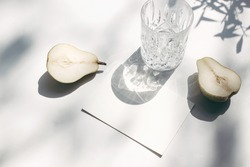 Summer stationery still life scene. Glass of water, cut pears fruit and olive tree branches long shadows. Blank paper, greeting card mock up. White table background in sunlight. Flat lay, top view.