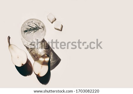 Summer stationery still life scene. Glasses of water, rosemary herb, cut pears fruit and ice cubes. Beige table background in sunlight. Vacation refreshment concept. Long harsh shadows. Flat lay, top.