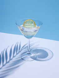 Summer stationery still life scene made with glass, dried lemon, drink, and trend palm shadow on blue pastel background. Summer vacation refreshment concept. Long shadow and refraction pattern.