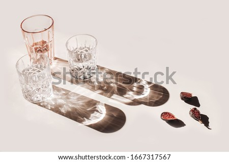 Summer still life scene. Glittering glasses of water or cocktails and cut figs fruit on pink table background in sunlight. Long harsh shadows. High angle. Refreshment, vacation concept.