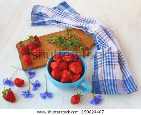 Summer still-life with blue cornflowers and fresh strawberries on a kitchen table