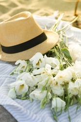 Summer straw hat with bouquet of white flowers on golden sand by the beach, romantic beach date vacation concept, travelling blogger, relaxation leisure time, resort beach picnic at sun set