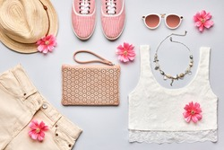 Summer street style. Fashion girl clothes accessories. Trendy sunglasses, gumshoes, top, handbag clutch, necklace hat, flowers. Creative urban summertime fashionable outfit