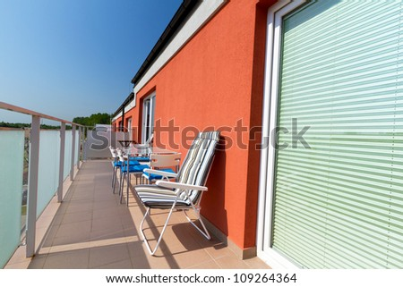 Summer sun at apartment balcony with deck chairs - stock photo