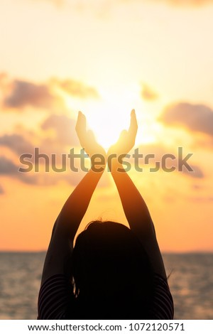 Summer sun June solstice concept and silhouette of happy young woman\'s hands relaxing, meditating and holding sunset against warm golden hour sky on the beach with ocean or sea background