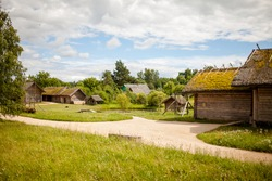 Summer sunny day in a russian village. The landscape depicts old wooden houses, trees and shrubs. Image with selective focus.