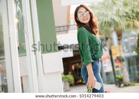 Summer sunny lifestyle fashion portrait of young stylish hipster Asia woman walking on the street, wearing cute trendy outfit