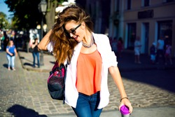 Summer sunny lifestyle fashion portrait of young stylish hipster woman walking on street,wearing cute trendy outfit,drinking hot latte,smiling enjoy weekends,travel with backpack,coffee,rest,lounge