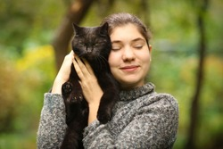 summer sunny photo of teenager girl hug blackcat close up outdoor photo
