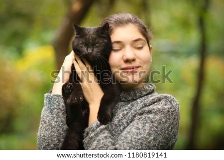 summer sunny photo of teenager girl hug blackcat close up outdoor photo