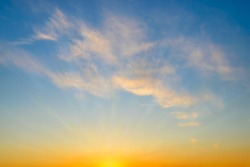 Summer sunrise sky with sunbeams and few golden translucent clouds. Beautiful dawn skyscape. Clear paradise sky at early morning. Calm blue heaven. Background.