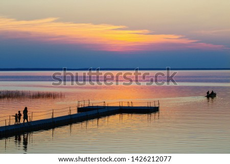 summer sunset on lake wit family and  boat #1426212077