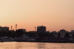 Summer sunset on the sea cost. City skyline in golden hour.