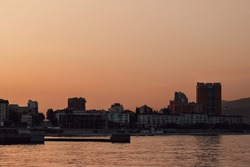 Summer sunset on the sea cost. City skyline in golden hour(orange color treatment).