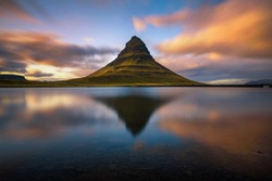 Summer sunset over the famous Kirkjufell mountain with reflection in a nearby lake in Iceland. Long exposure.