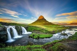 Summer sunset over the famous Kirkjufellsfoss Waterfall with Kirkjufell mountain in the background in Iceland. Long exposure.