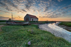 Summer sunset over the old coal barn at Thornham on the Norfolk coast