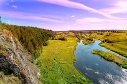 summer sunset over the river and forest. beautiful view from a cliff to a river with islands and a shore with young green grass